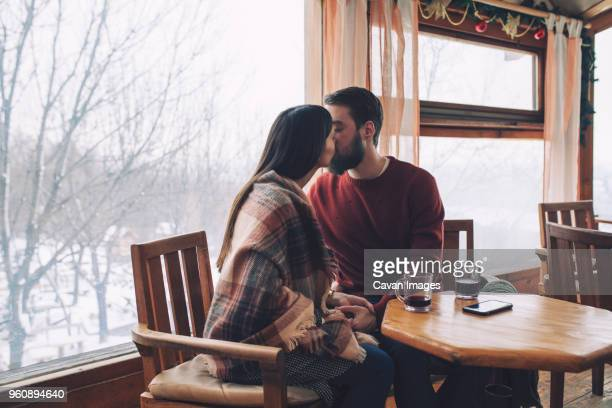 young couple kissing while sitting in cafe during winter - shawl stock pictures, royalty-free photos & images