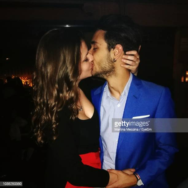 young couple kissing while standing in nightclub - embrasser sur la bouche photos et images de collection