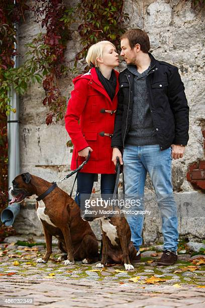 young couple kissing with pet dogs looking away - ラッペーンランタ ストックフォトと画像