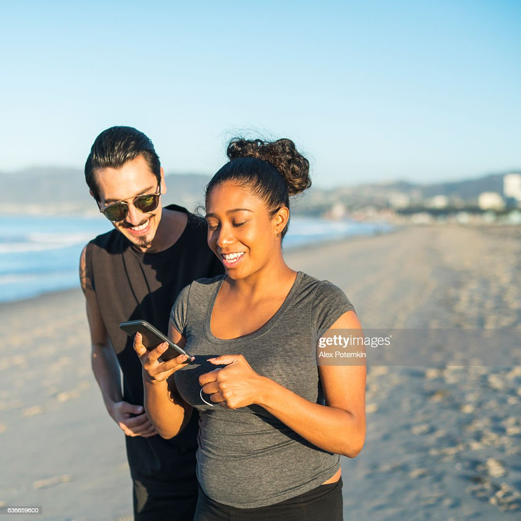 Young couple, Latino man and girl, take selfie on beach : Stock Photo