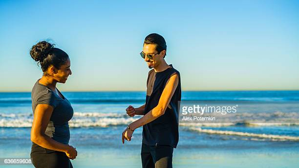 young couple, latino man and girl, talking on the beach - alex potemkin or krakozawr latino fitness stock photos and pictures