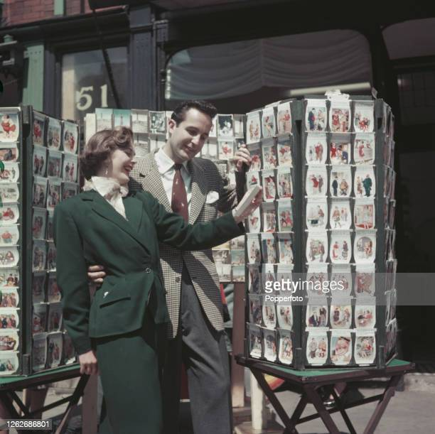 A young couple laugh as they view a carousel of saucy postcards created by the English graphic artist Donald McGill at a postcard shop in the seaside...