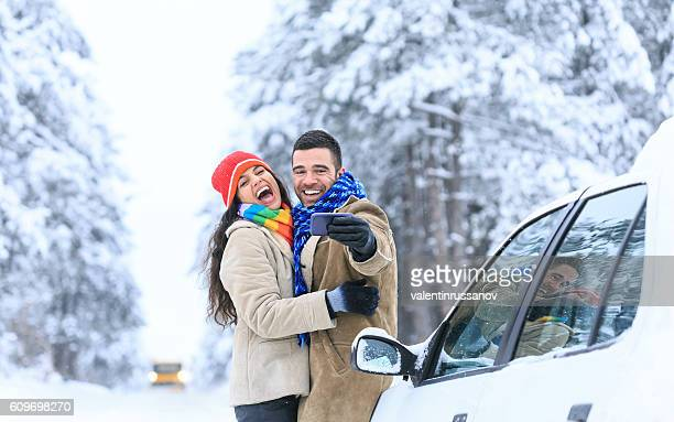 Young couple laughing and making selfie on snow footpath