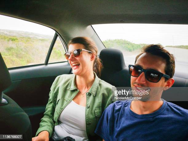 young couple laughing in car during road trip - taken on mobile device stock photos and pictures