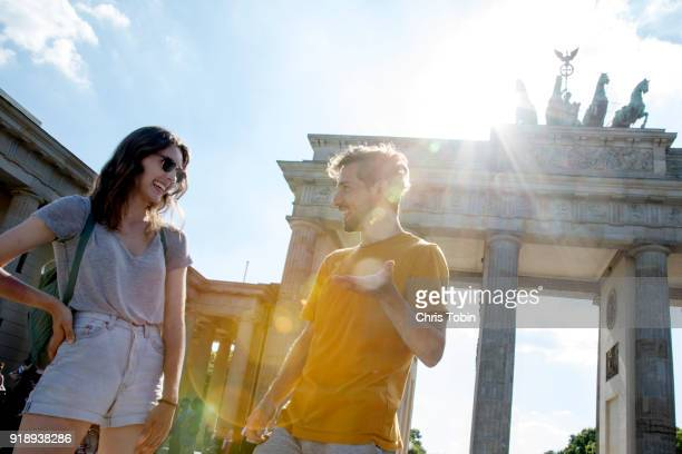 young couple laughing in front of brandenburg gate brandenburger tor with lens flare - berlin stock-fotos und bilder