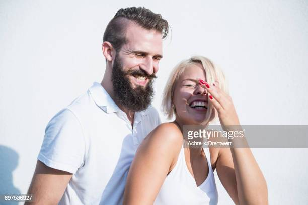 Young couple laughing in front of wall, Bavaria, Germany