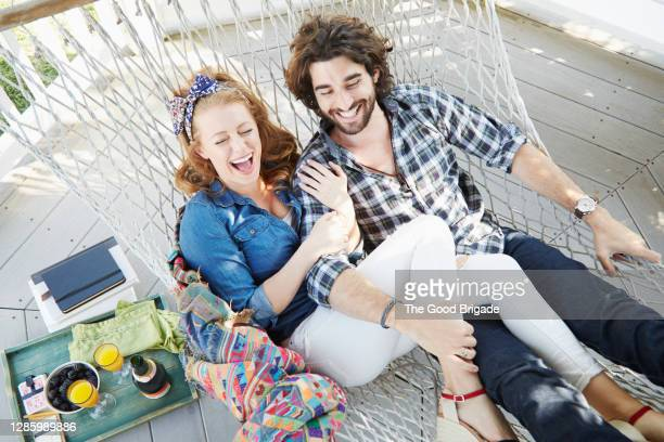 young couple laughing in hammock - pergola photos et images de collection