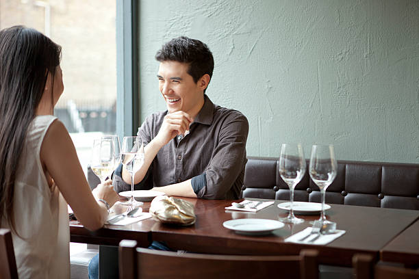 young couple laughing in restaurant - asian couple dating stock pictures, royalty-free photos & images