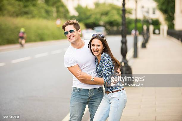 Young couple laughing on city street, London, UK