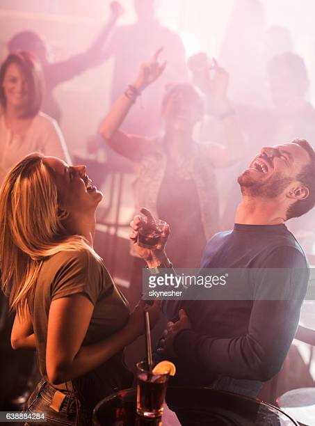 Young couple laughing while spending night at disco club.