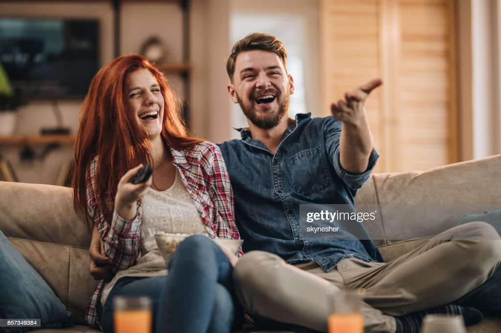 Young couple laughing while watching TV at home. : Stock Photo