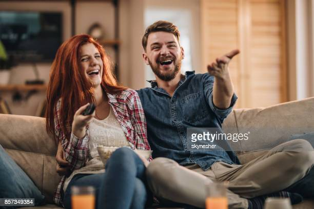 Young couple laughing while watching TV at home.
