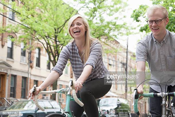 young couple laughing whilst cycling along street - queens new york city stock pictures, royalty-free photos & images