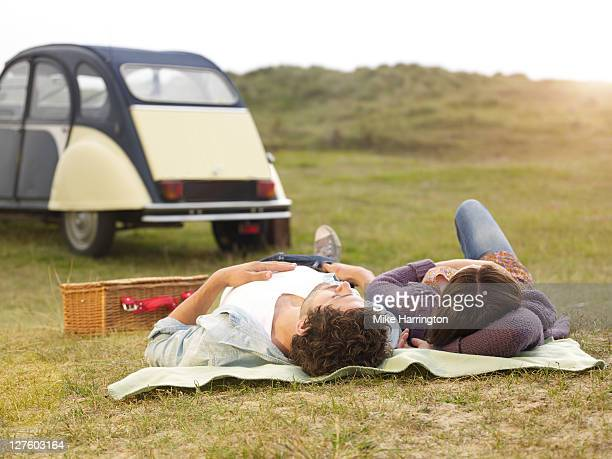 Young couple laying down gazing up a sky