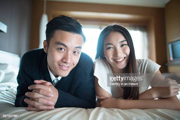 Young couple laying on the bed smiling.