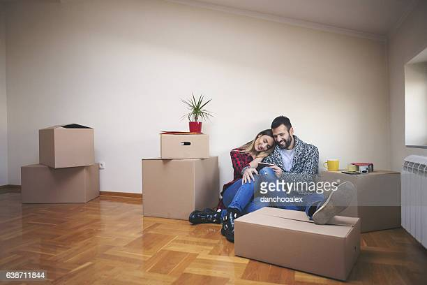 Young couple laying on the floor of their new house