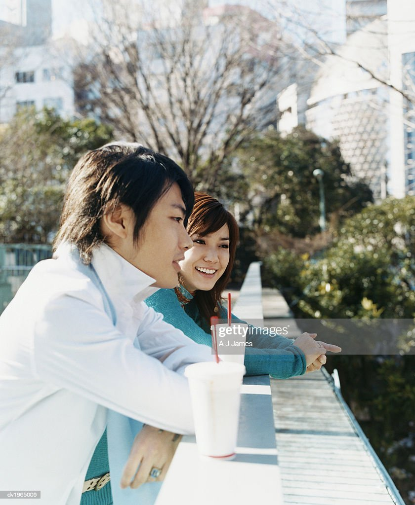 Young Couple Leaning Against a Railing in a Park : Stock Photo