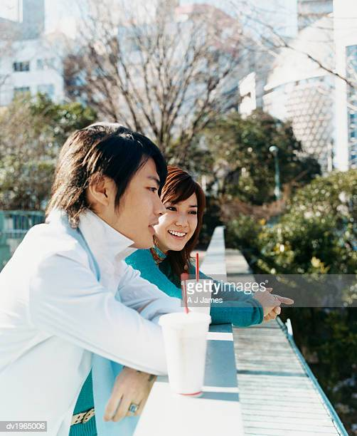 Young Couple Leaning Against a Railing in a Park