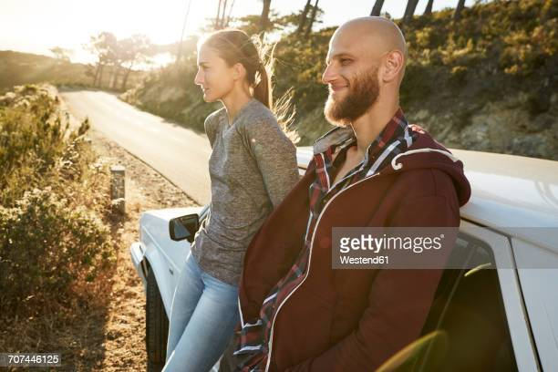 Young couple leaning against car at roadside