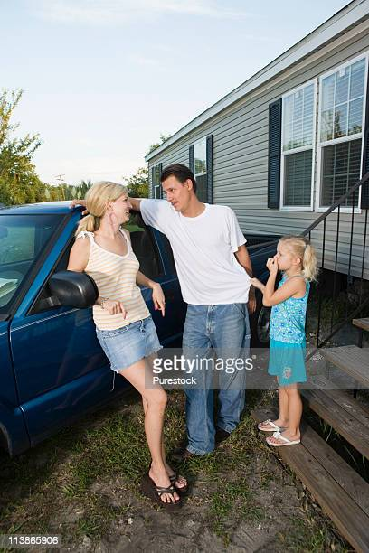 Young couple leaning against old pickup truck with daughter in front of trailer home