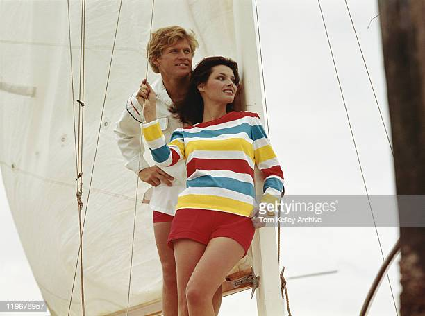 Young couple leaning against sail