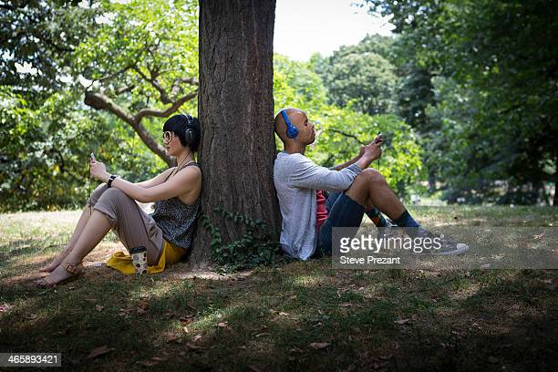 Young couple leaning against tree trunk