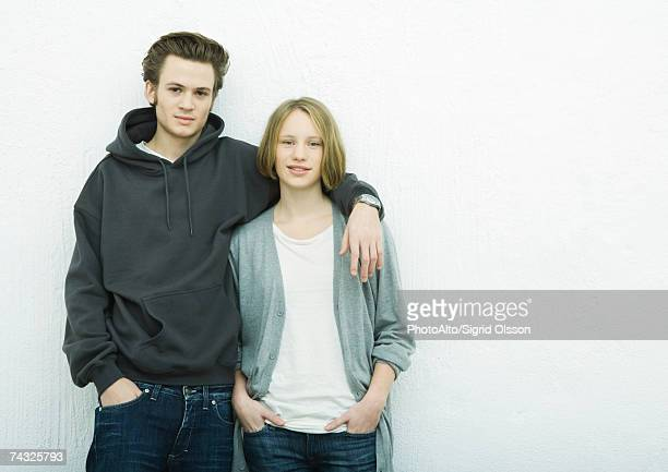 Young couple leaning against wall, looking at camera, portrait