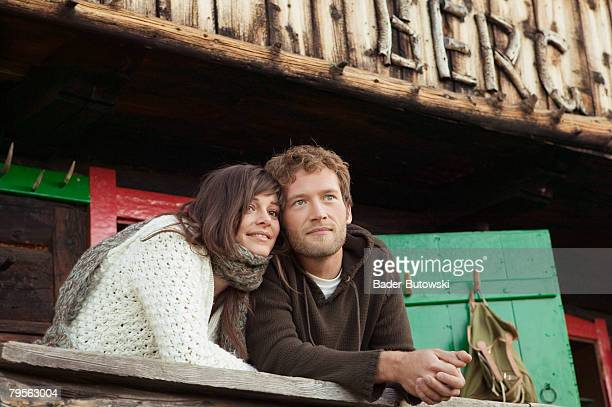 Young couple leaning on wooden rail in front of alpine hut