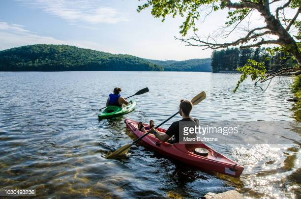young couple leaving for a ride in kayak on the lake during summer day - hot women on boats stock pictures, royalty-free photos & images