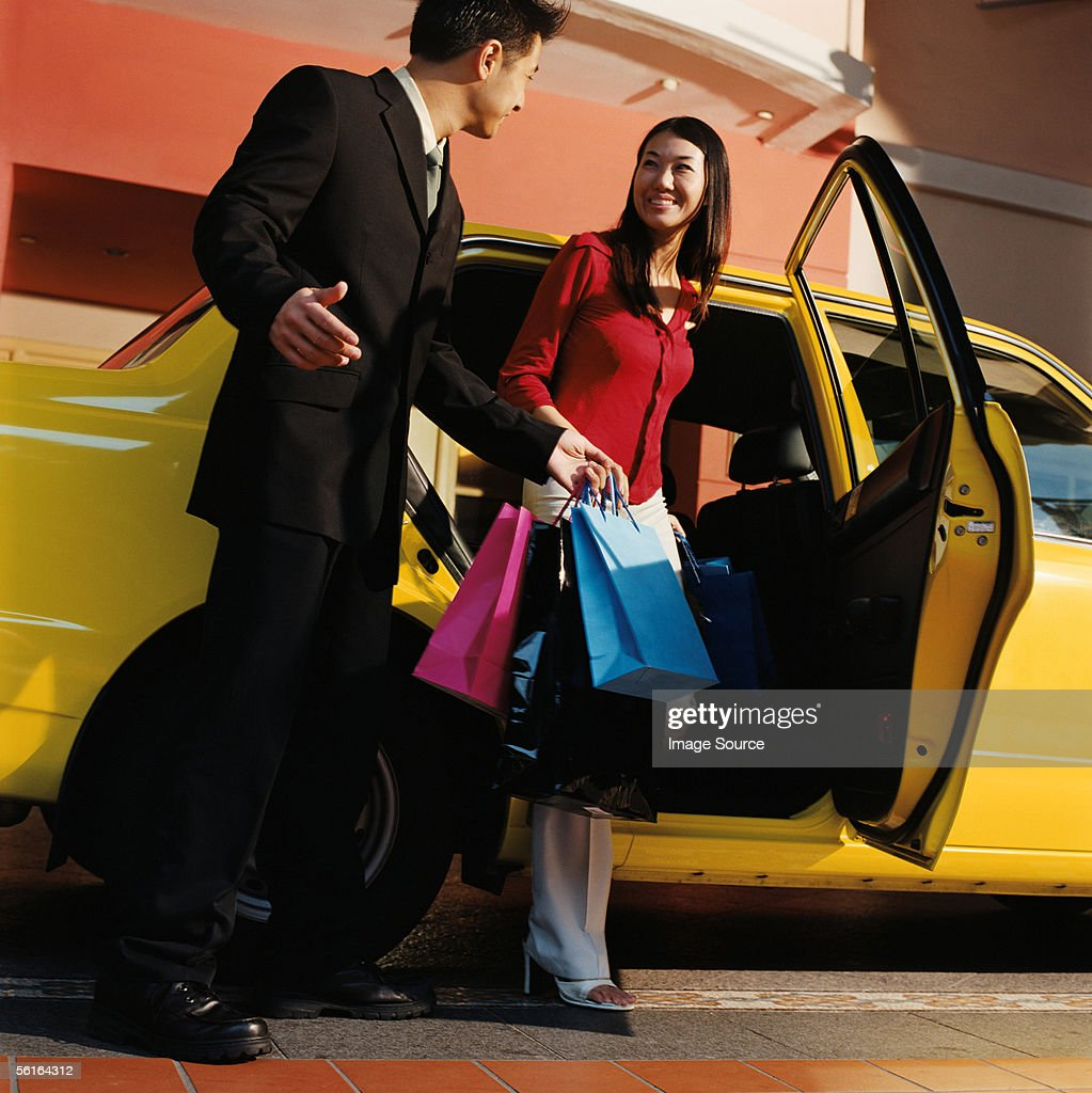 Young couple leaving taxicab : Stock Photo