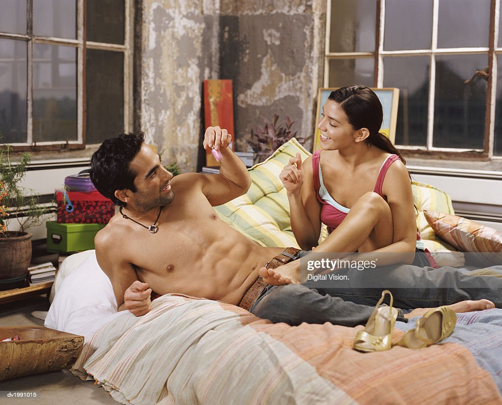Young Couple Lie on a Bed Talking to Each Other : Stock Photo