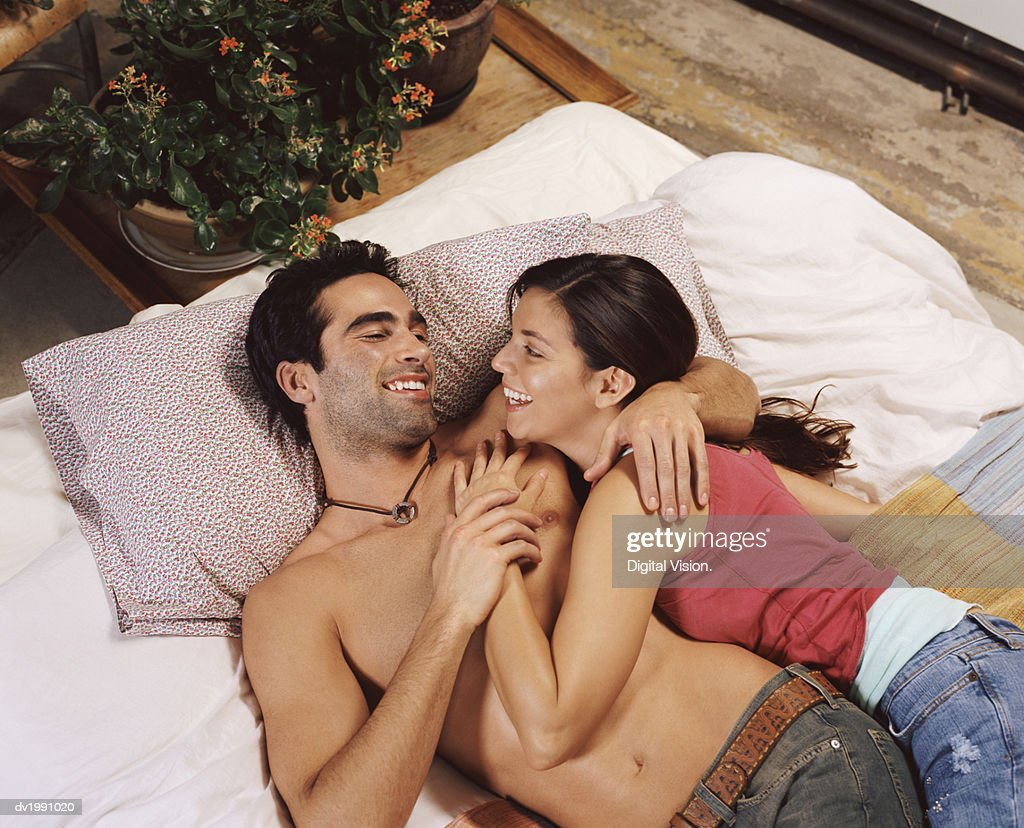 Young Couple Lie on a Futon Embracing and Laughing : Stock Photo