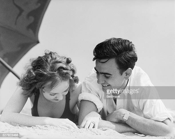 Young couple lie on the beach under an umbrella. They are shown on their stomachs, in a head-and-shoulders front view. Undated photograph, circa...