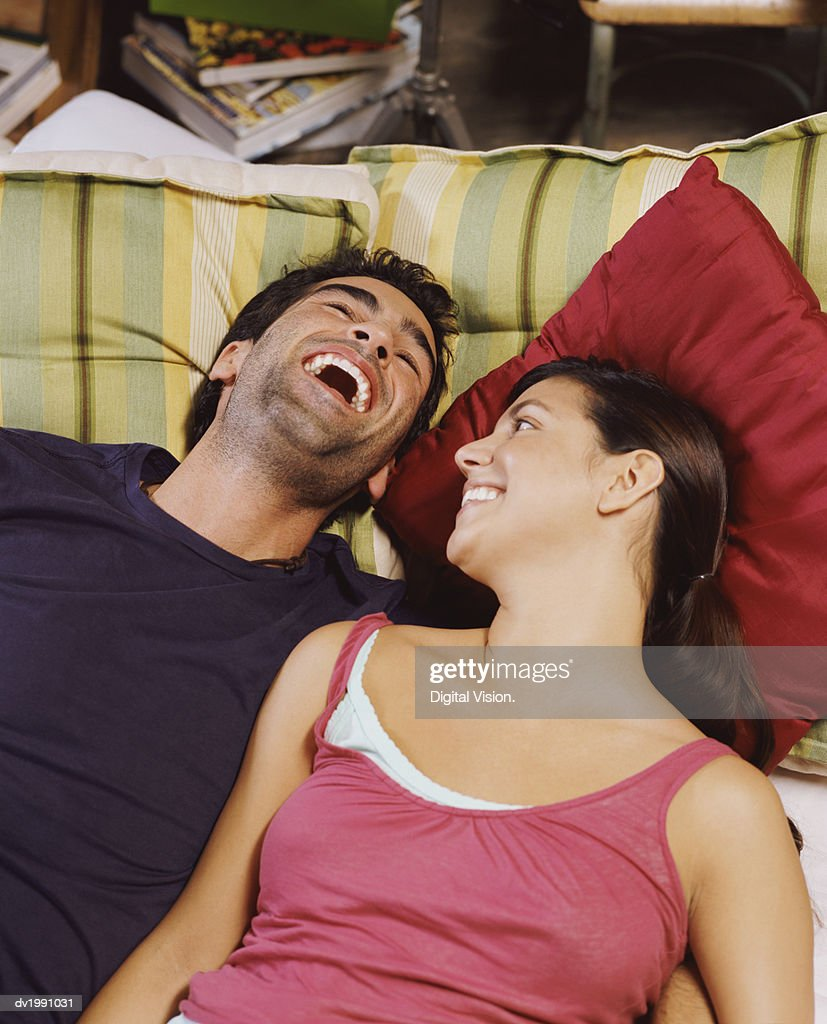 Young Couple Lie Side by Side on a Bed, the Man Laughing : Stock Photo