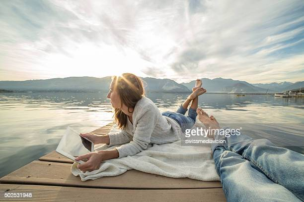 Young couple lies on jetty above lake, uses digital tablet