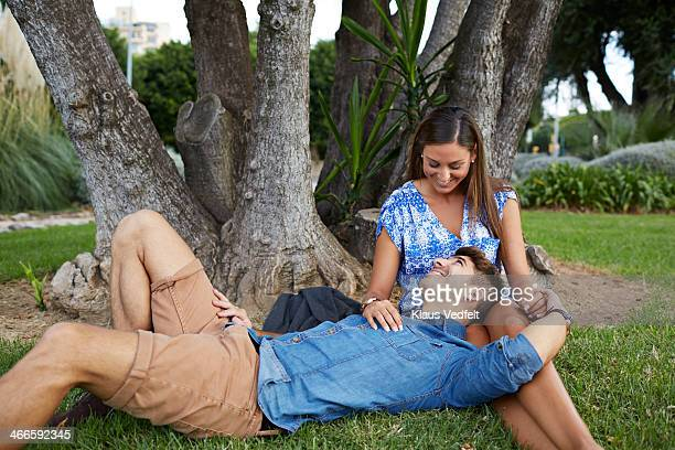 young couple lies under neath big tree in park - klaus vedfelt mallorca stock pictures, royalty-free photos & images
