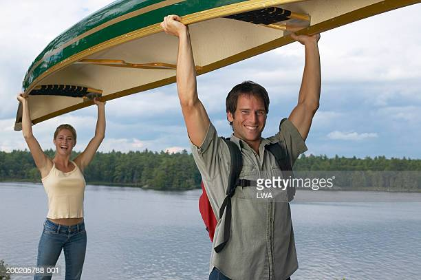 Young couple lifting canoe near lake, smiling, portrait