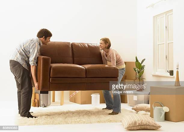 Young couple lifting sofa.