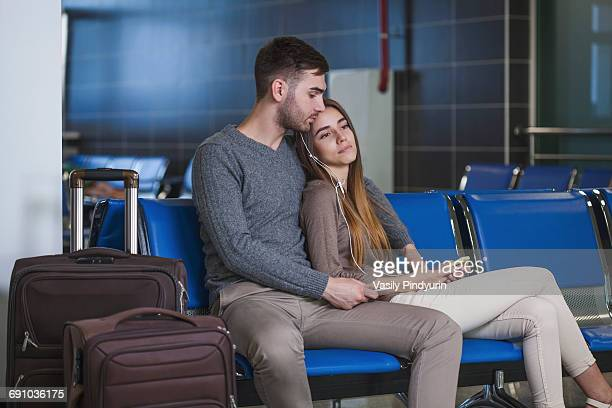 Young couple listening music through mobile phone while waiting in airport