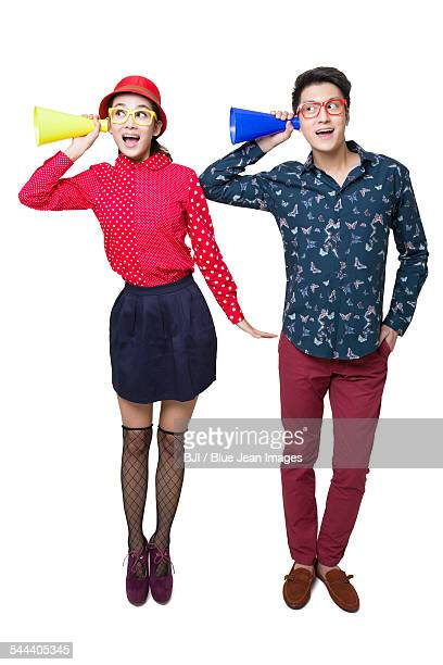 Young couple listening through megaphones