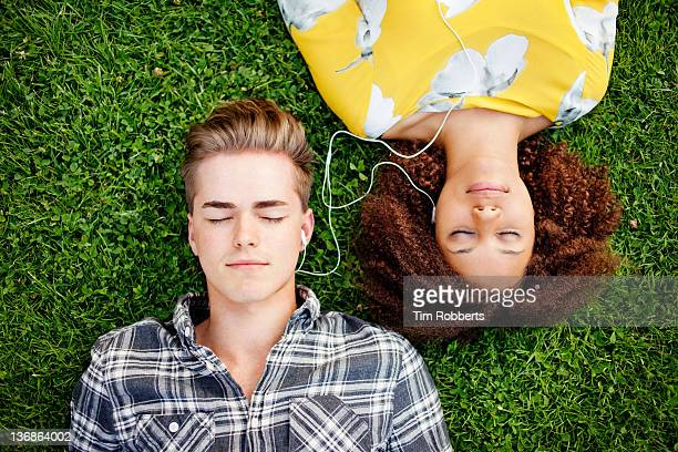 young couple listening to and sharing music. - sharing stock pictures, royalty-free photos & images