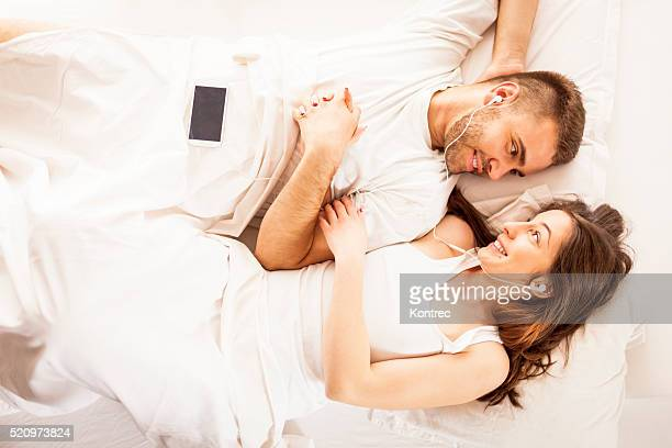 young couple listening to music in bed - good morning kiss images stock photos and pictures