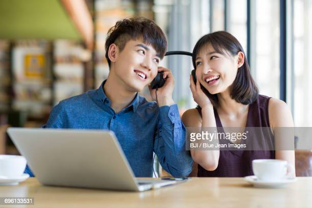 Young couple listening to music in caf
