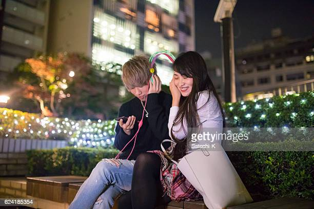 young couple listening to music in christmas lights - christmas music stock pictures, royalty-free photos & images