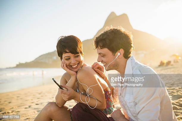young couple listening to music, ipanema beach, rio, brazil - rio de janeiro - fotografias e filmes do acervo