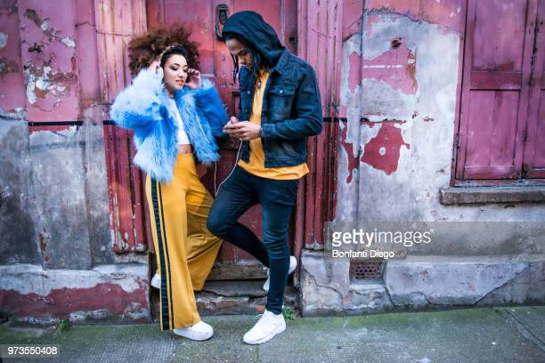 young couple listening to music through headphones on smartphone - street style stock pictures, royalty-free photos & images