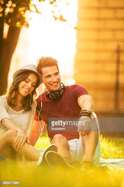 Jeune couple, écouter de la musique ensemble dans le parc