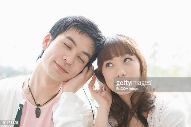 Young couple listening to music with headphones