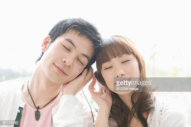 Young couple listening to music with headphones, with eyes closed