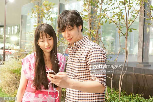 Young couple listening to music with smartphone